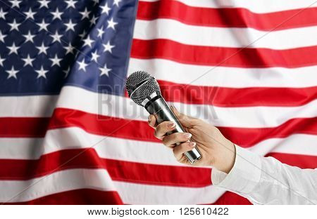 Female hand with microphone on USA National Flag background