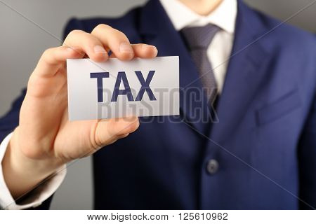 Tax Concept. Businessman with business card, close-up