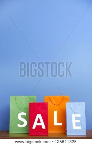 Word sale made with paper bags on blue wall background