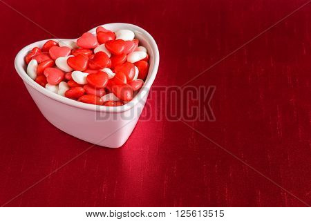 Heart candy in a white heart dish on a red background, for Valentine's Day