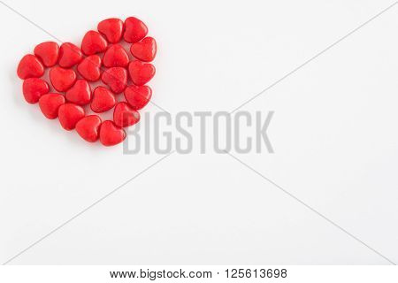 Red heart candy in a heart shape on a white background