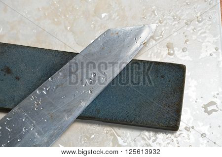 kitchen knife and grindstone on tile floor