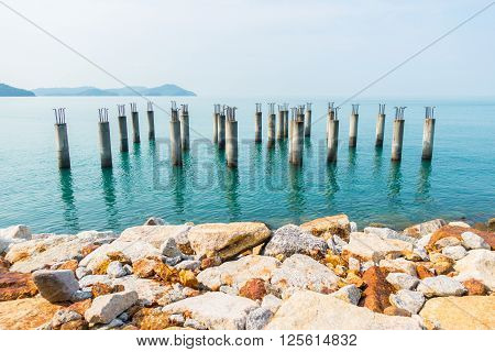 Concrete piles with iron from an unfinished building in the blue waters around Langkawi island Malaysia