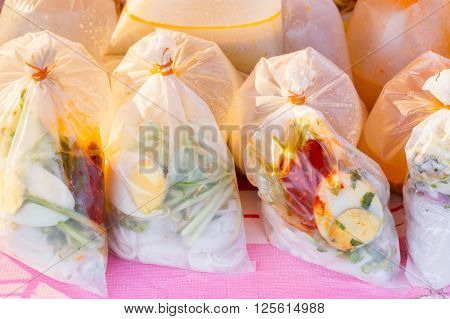 Malaysian style take away noodle dish in transparent plastic bag on a local market