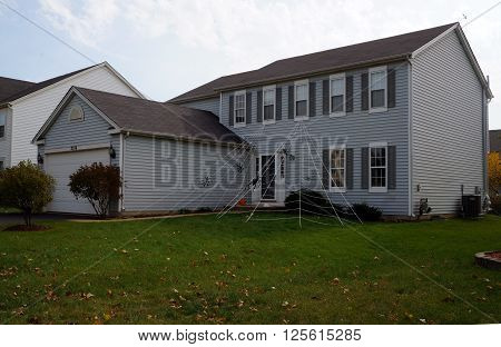 JOLIET, ILLINOIS / UNITED STATES - OCTOBER 21, 2015: A suburban tract home is decorated with a giant spider web for Halloween.