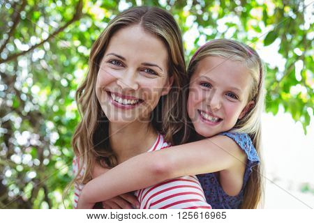 Portrait of smiling mother giving piggy-back to daughter