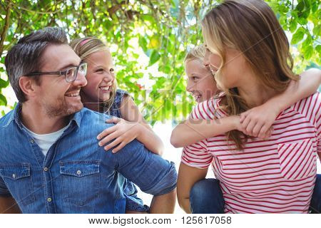 Smiling parents giving piggy back to children while standing outdoors