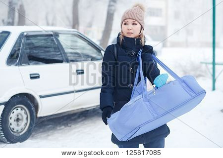 Young mother with her baby child in the cradle bag outside the winter time in a frosty mist, car background, need help with carriage.