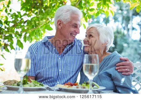 Cheerful retired couple with arm around while sitting at table