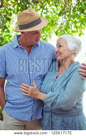 Smiling senior couple with arm around while talking outdoors