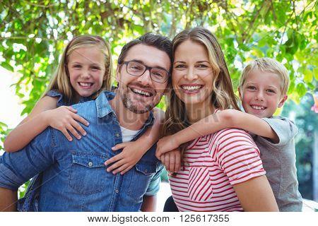 Portrait of happy parents giving piggy back to children