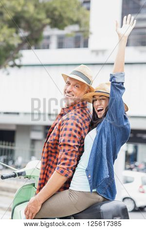 Portrait of excited couple on moped with woman raising hand