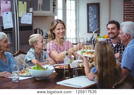 Multi generation family with grandparents sitting at dining table