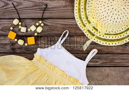 Summer children's clothing: dress, hat and beads on wooden background. Toned image.
