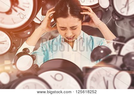 Worried businesswoman holding her head against black background