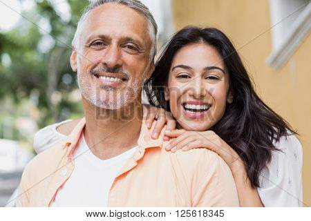 Portrait of cheerful couple looking away in city