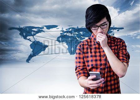 Surprised hipster watching his phone against view of a global map