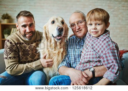 Portrait of senior man, his son, grandson and dog