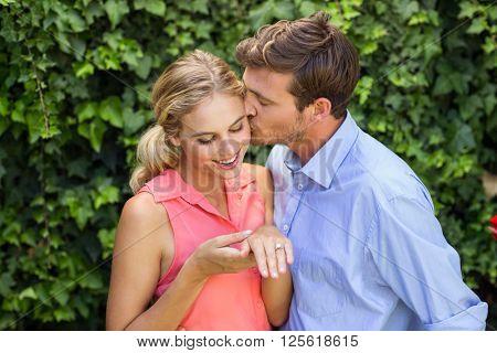 Happy romantic man kissing woman at front yard