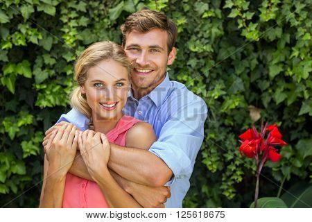 Portrait of smiling couple embracing at front yard