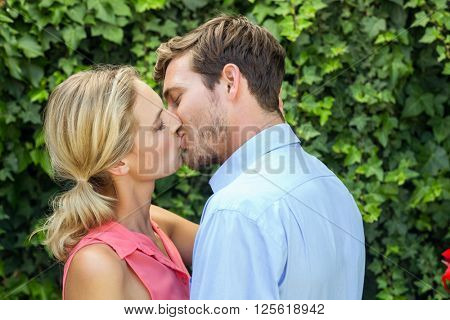 Happy romantic couple kissing at front yard