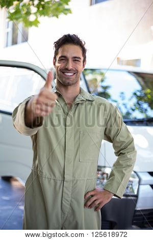 Portrait of smiling pesticide worker showing thumbs up while standing by van