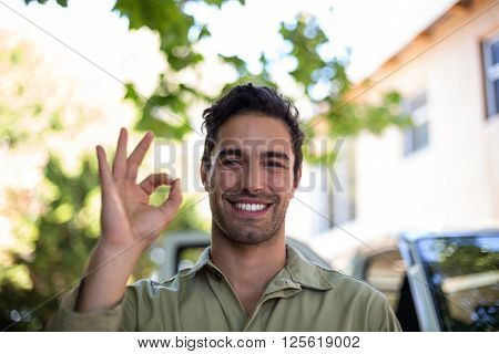 Close-up portrait of smiling pesticide worker showing ok sign while standing by van