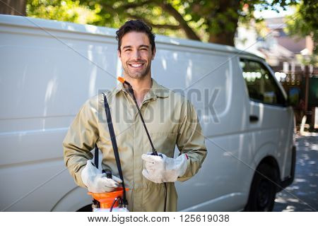 Portrait of smiling worker with pesticide sprayer while standing by van