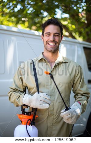 Portrait of happy worker with pesticide sprayer while standing by van