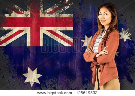 Smiling businesswoman with crossed arms against australia flag in grunge effect