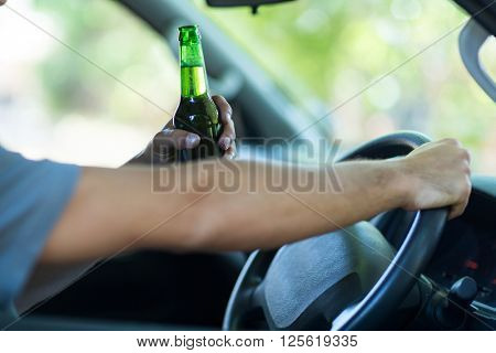 Cropped hands of man with alcohol while sitting in car