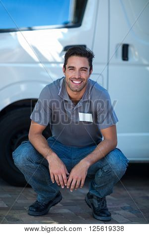 Portrait of smiling delivery man crouching by van