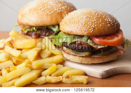 Fastfood burgers and fries lies on wood table