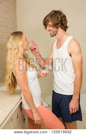 Cute couple getting ready and applying cream in the kitchen
