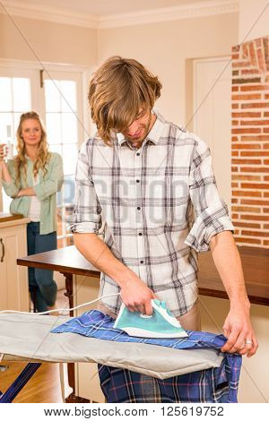 Handsome man ironing a shirt while girlfriend watching in background in the living room