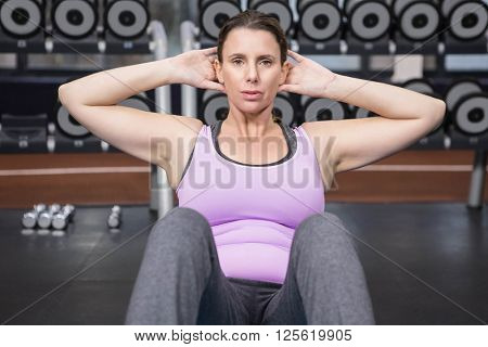 Woman doing abdominal crunches on mat at the gym