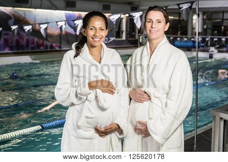 Pregnant women with bathrobe touching their bellies at the swimming pool