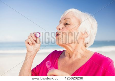 Senior woman making bubbles with a bubble wand on the beach