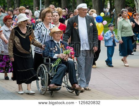 VOLGOGRAD RUSSIA - MAY 9 2010: World War II veteran in a wheelchair and accompanied by relatives on Victory Day celebration on the Avenue of Heroes in Volgograd