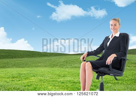 Businesswoman sitting on swivel chair in black suit against blue sky over green field