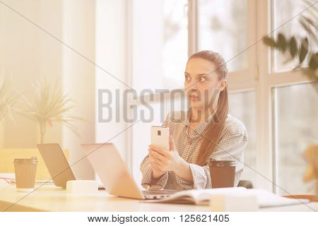 Tired or suprised freelance woman making pictures of laptop computer's data and looking away while sitting at table in office interior.