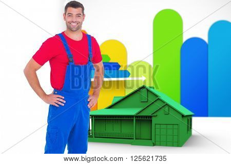 Happy handyman in overalls with hands on hip against house with energy rating background