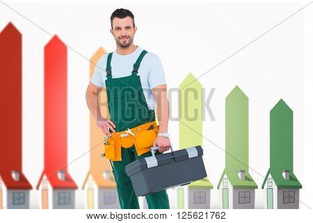 Smiling carpenter with toolbox against seven 3d houses representing energy efficiency