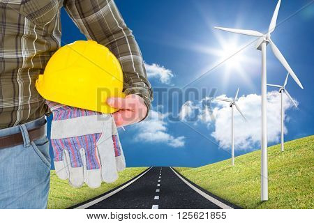 Manual worker holding helmet and gloves against road leading out to the horizon with wind turbines either side