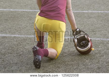 American football player kneeling on the field and holding the red helmet