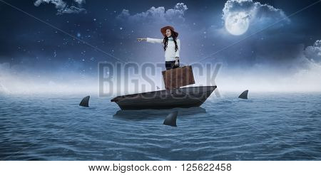 Smiling Asian woman holding luggage pointing somewhere against sharks circling small boat in the sea
