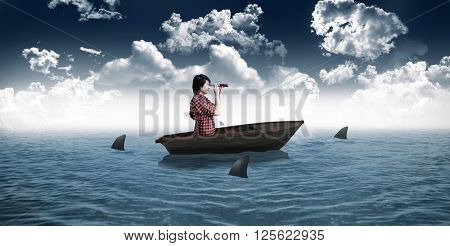 Hipster looking through a telescope against sharks circling small boat in the sea
