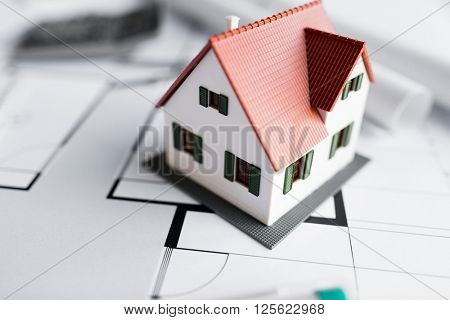 architecture, building, construction, real estate and home concept - close up of living house model on blueprint