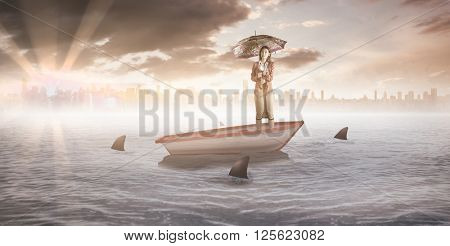 Businesswoman with an umbrella against sharks circling a small boat in the sea