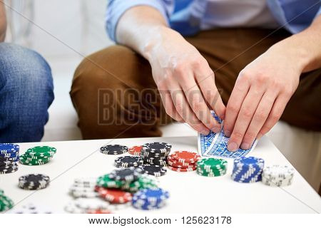 leisure, games, friendship, gambling and entertainment - close up of male hand with playing cards and chips at home